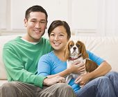 An attractive young asian couple sitting on a couch together and holding a dog.  They are smiling at the camera.  Horizontally framed shot.