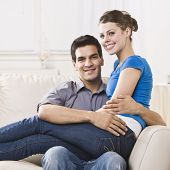 An attractive young couple relaxing together in their home.  The woman is sitting on the man's lap a