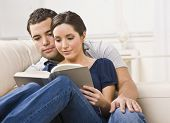A young, attractive couple is seated together on a couch and are reading a book together.  They are