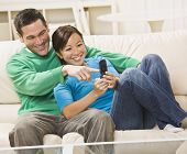 Mixed race couple laughing and looking at a cell phone together. horizontal