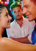 Jealous man looking at dancing couple, flirting girlfriend in nightclub.