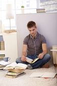 Student studying at home, sitting on floor with books and notes, listening to music via headphones.
