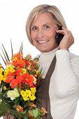 mature florist holding bouquet