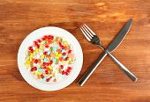 a lot of pills in a plate with knife and fork on wooden background close-up