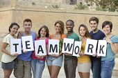 Group of young people holding teamwork sign smiling