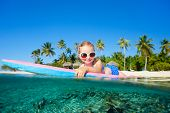 Adorable little girl on tropical vacation swimming
