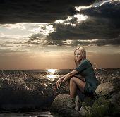 Beautiful Blonde Woman Sitting near the Sea