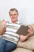 Senior Caucasian Man With Tablet Device  Thumb Is Up  Domestic Room, Sofa poster
