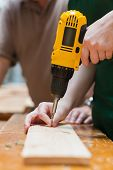 Holding a nail and holding the driller while drilling a hole in a wooden board