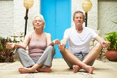 Senior Couple Meditating Outdoors At Health Spa