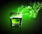 Glass of green absinth with fume going out