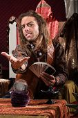 picture of seer  - Handsome male fortune teller with tarot cards and crystal ball - JPG