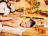 Woman getting massage with ear candle in bamboo spa.