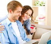 Internet Online Shopping. Happy Smiling Couple Using Credit Card to Internet Shop. Young couple with laptop and credit card buying online. E-shopping. Paying Online