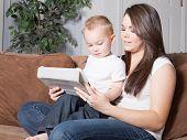 Jonge moeder weergegeven: peuter te lezen op Tablet PC