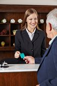 Smiling female receptionist in hotel greeting a senior man