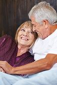 Happy senior couple having fun in bed in a hotel room