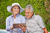 Two happy senior people sitting with tablet computer at pool