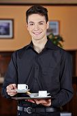 Smiling waiter bringing hot cup of coffee in a caf�?�?�?�©