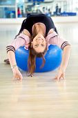 stock photo of bending over backwards  - Gym woman bending backwards over a pilates ball - JPG