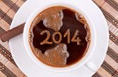 New year 2014 handwritten on the coffee surface in the cup, with coffee foam texture