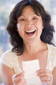 stock photo of lottery winners  - Woman with winning lottery ticket excited and smiling - JPG