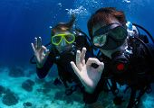 Underwater shoot of a couple diving with scuba and showing ok signal. Focus on a man's hand