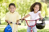stock photo of brother sister  - Brother and sister outdoors with scooter and bicycle smiling - JPG