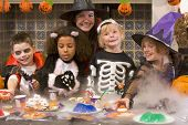 Four Young Friends And A Woman At Halloween Eating Treats And Smiling