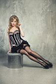 Sexy Blond Pin Up Girl Sitting On A Pouf Over Grey Obsolete Background