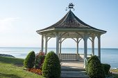 image of gazebo  - Gazebo surrounded by small trees and flowers by Lake Ontario - JPG