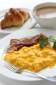 breakfast with scrambled eggs, crispy bacon, croissant and cafe au lait