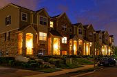 stock photo of row trees  - Nicely illuminated townhouse at night with a blue sky - JPG