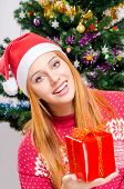 stock photo of merry chrismas  - Girl in front of Christmas tree with gift - JPG