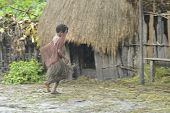Papuan Girl From Dani Tribe  Hurries To Hide From A Rain Under A Roof.