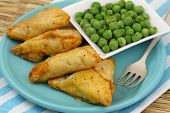 Vegetarian samosas and green peas, close up