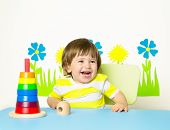 stock photo of playgroup  - Happy cheerful baby at kindergarten or playgroup playing with pyramid toy - JPG