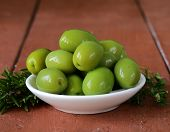 stock photo of kalamata olives  - green marinated olives in  bowl on a wooden table - JPG