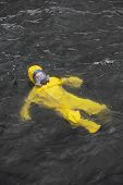 accident on the sea  - worker in protective suit in water