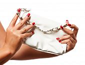 closeup of the woman�?�¢??s hand wearing red half moon nail art manicure with white leather bag w