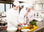 Chefs preparing a dish in a commercial kitchen