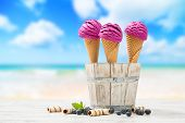 Three icecreams with blueberries and beach blur background
