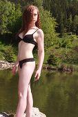 Beautiful young redhead posing in a black bikini