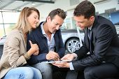 pic of 35 to 40 year olds  - Couple signing car purchase order on digital tablet - JPG