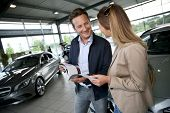 Couple looking at dealership brochure to choose vehicle