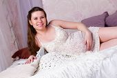 Pregnant Woman Lying In Bed And Smiling
