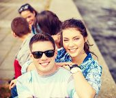 summer holidays, relationships and teenage concept - smiling teenagers having fun outside