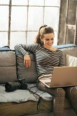 Smiling Young Woman With Modern Dslr Photo Camera Using Laptop I