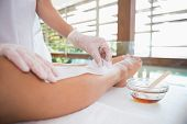 Woman getting her legs waxed by beauty therapist in the health spa