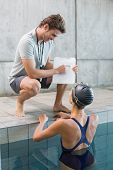 Swimmer talking to her coach poolside at the leisure center